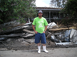 Pointe-au-Chien tribe member in front of flooded, damaged home