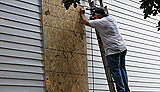 photo of person boarding up house