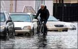 Ken Freedman of WFMU biking in a flooded street