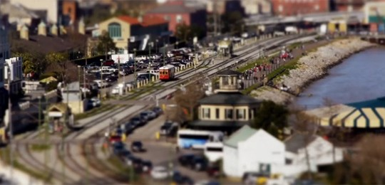 A frame from tilt shift video, showing streetcar along the river