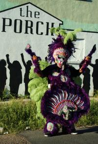 A full dress Mardi Gras Indian stands outside The Porch