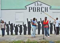 A shot of The Porch's mural shows sillohuettes of children as 3 real life children perform
