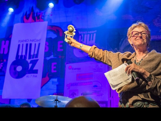 Deborah Harkins of WWOZ's Board of Directors with the evening's award for Henry Butler at Piano Night 2015 [Photo by Marc PoKempner]