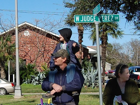 Dad with kid on his shoulders waits for parade to pass