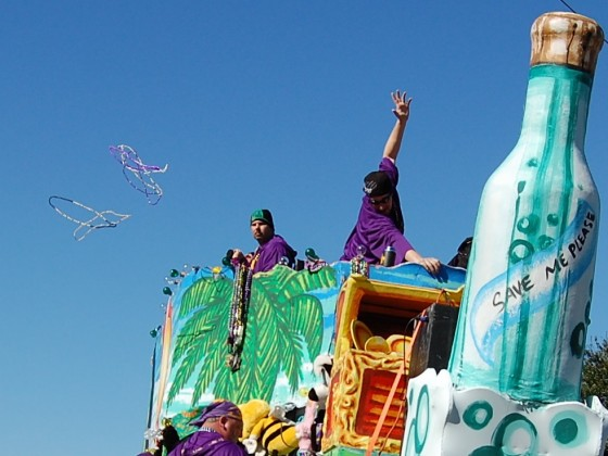 Float featuring giant bottle figurehead and showboating krewe riders