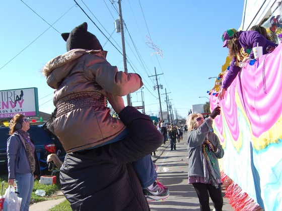 bundled up kids on piggyback approach carnival float