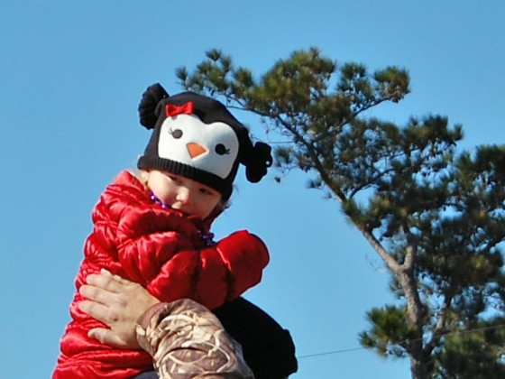 dad in camo jacket holds stylishly bundled toddler aloft