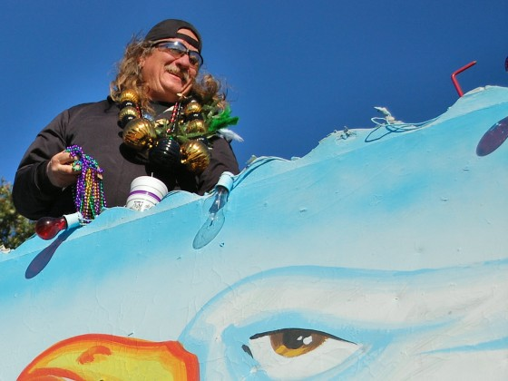 Krewe rider with fistful of beads atop seagull float