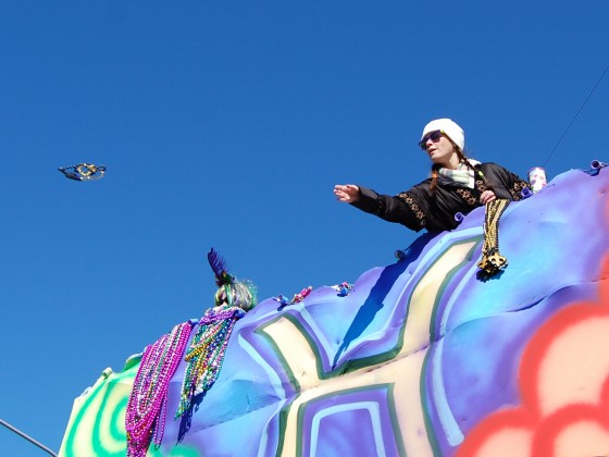 Lady rider tosses beads from upper float deck