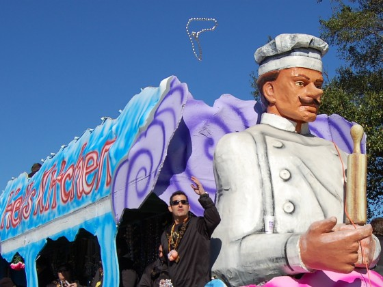 Rider tosses beads from a  'Hell's Kitchen'-themed float